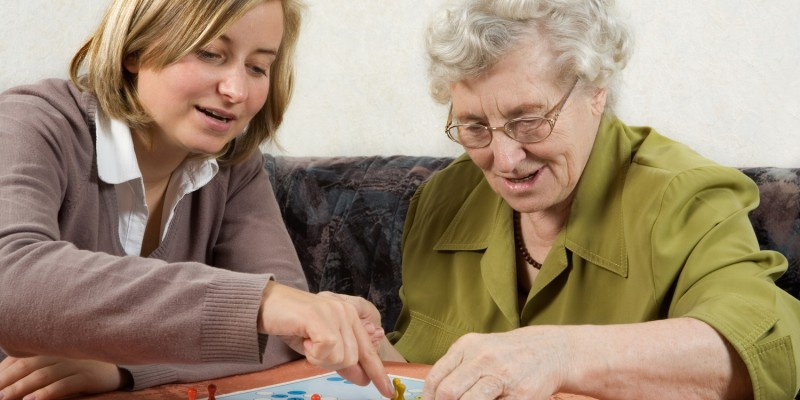 Pflegerin mit Seniorin zu Hause