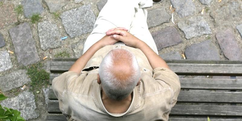 Senior sitzt auf Holzbank