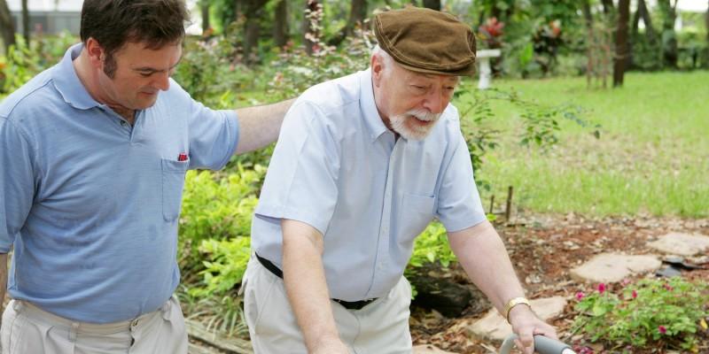 Mann begleitet einen älteren Herrn mit Rollator