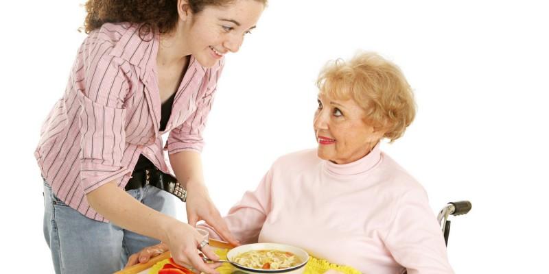 Junge Frau bringt Seniorin das Essen